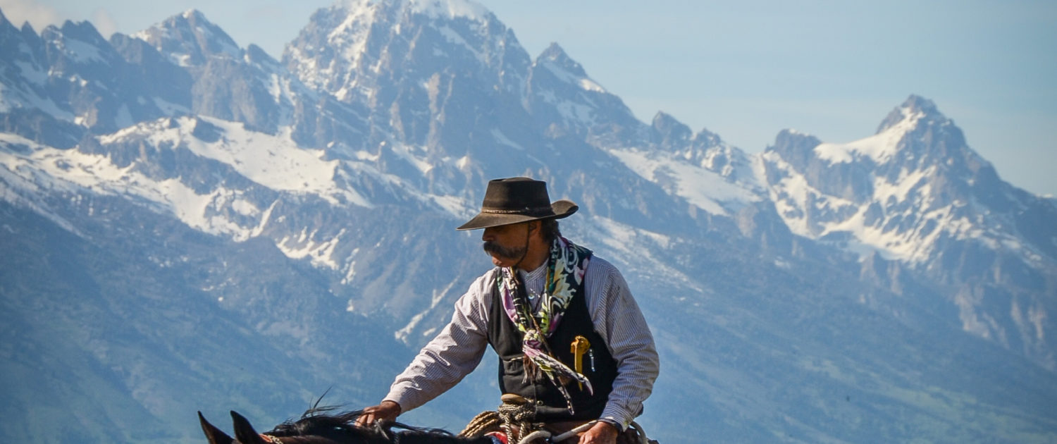 cowboy on horseback with Grand Tetons in background