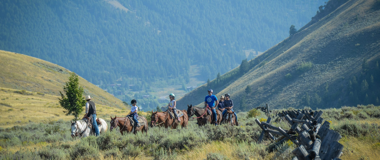 group of people horseback riding through Jackson Hole valley