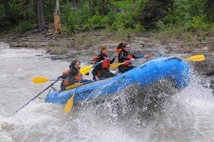 several people paddling through rapids on raft